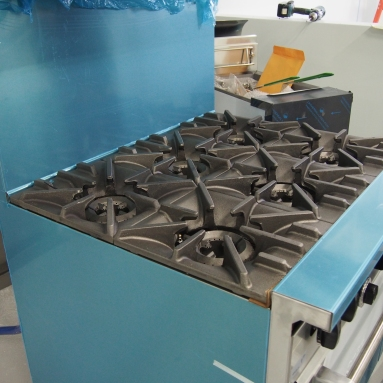 gas-fired 6 burner stove with gas fryer in background
