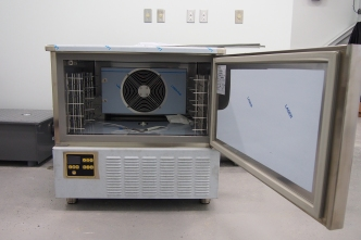 a photo of a blast chiller with the door open to the right and the interior exposed
