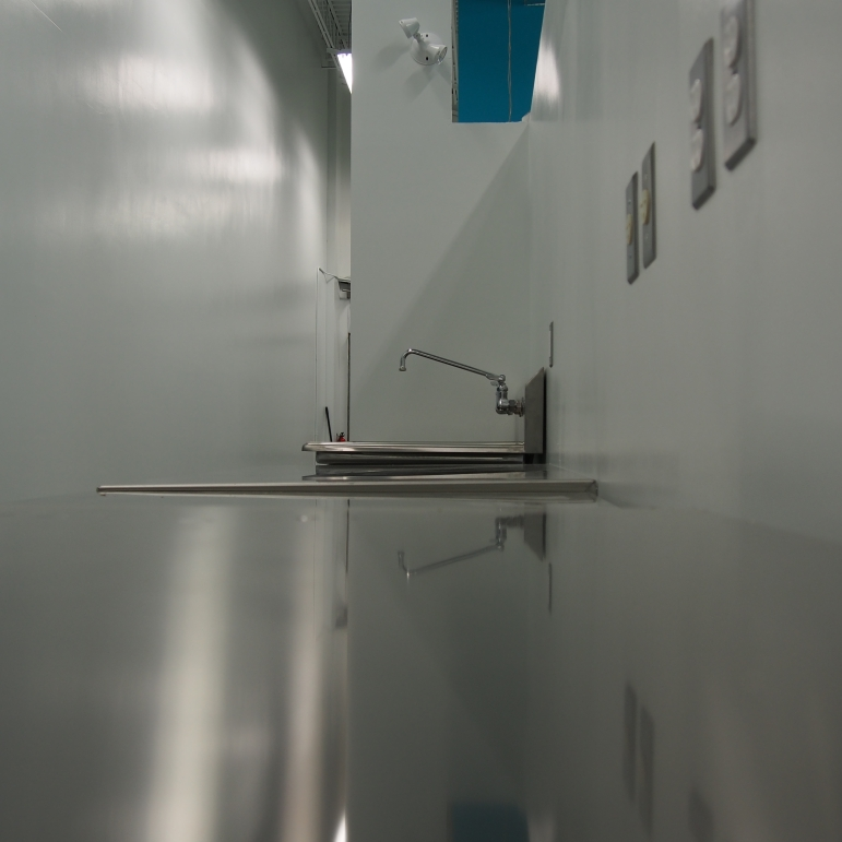 reflection of a sink fixture on a stainless steel surface