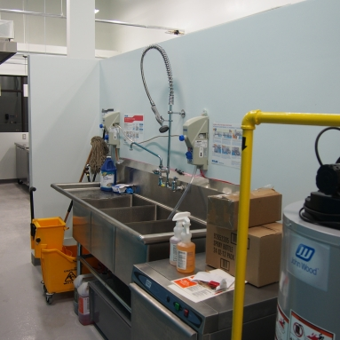 three compartment sink with containers of cleaning chemicals connected by tubes for use