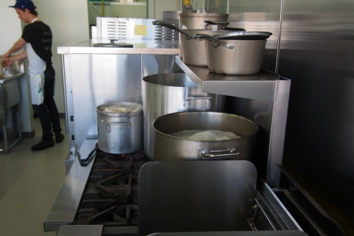 pots on top of a gas stove top boiling away