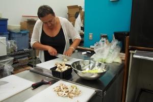 Cauldron Food School student slicing mushrooms.