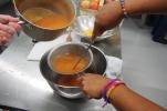 Straining the blended peaches.